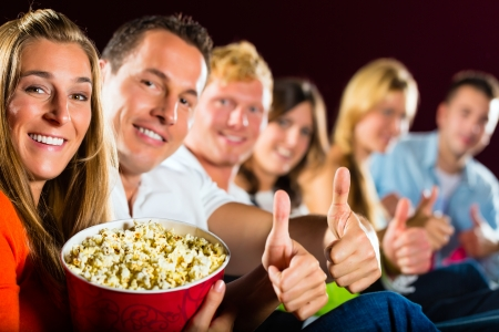 People see a movie in the cinema and have fun they smile at the camera photo