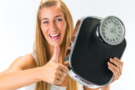 Diet and weight, young woman with a weight scale, she is happy about her success