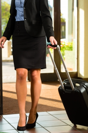 Businesswoman arriving at Hotel with her suitcases photo