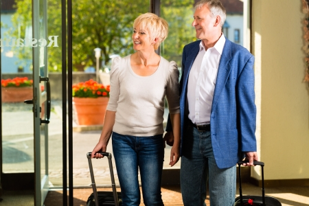 arriving: Senior man and woman - married couple - arriving at Hotel with their luggage