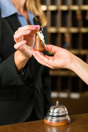 Reception - Guest checking in a hotel at the front desk, the room key is handed over Stock Photo - 18451918