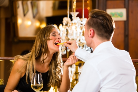 couple dining: Couple - man and woman - in a fine dining restaurant they eat fast food and fries - a large chandelier is in Background Stock Photo