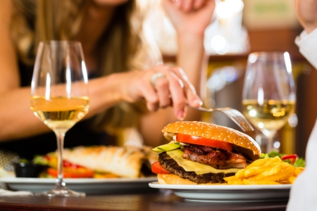 cheese burgers: Couple - man and woman - in a fine dining restaurant they eat fast food, burger and fries, closeup