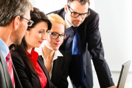 Business - Four professionals in office in business attire looking at laptop screen working together Stock Photo - 18452112