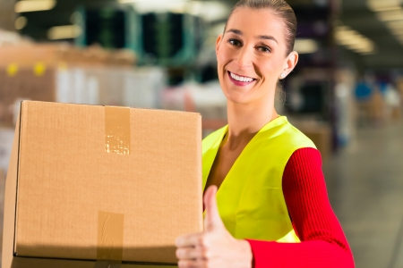 female worker with protective vest holds package, standing at warehouse of freight forwarding company photo