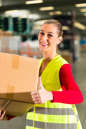 female worker with protective vest holds package, standing at warehouse of freight forwarding company Stock Photo - 18451775