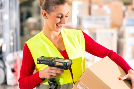Female worker with protective vest and scanner, scans bar-code of package, standing at warehouse of freight forwarding company photo