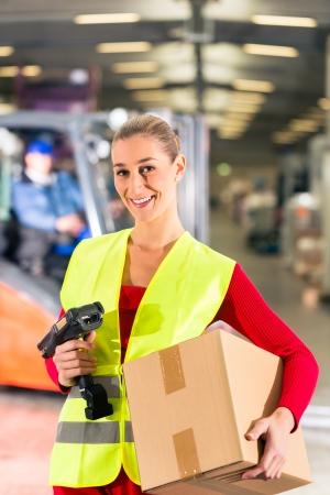forwarding: Mujer trabajando con chaleco antibalas y un esc�ner, tiene paquete, situ�ndose en el almac�n de la empresa de transporte de carga, sonriendo Foto de archivo