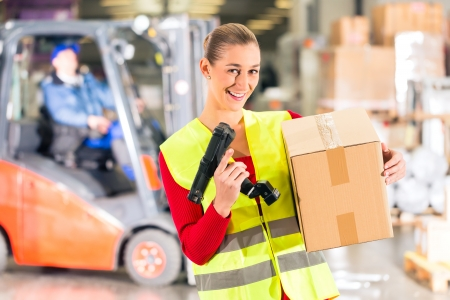 barcode scanner: Female worker with protective vest and scanner, holds package, standing at warehouse of freight forwarding company, smiling