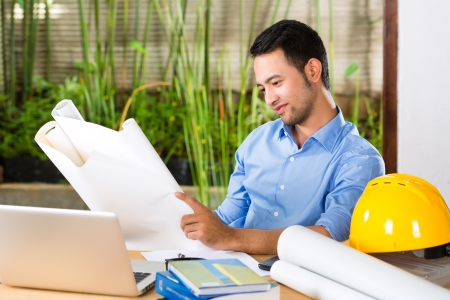 Freelancer - Architect working at home on a design or draft, on his desk are books, a laptop and a helmet or hard hat Stock Photo - 18452138