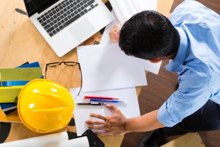 freelancer: Freelancer - Architect working at home on a design or draft, on his desk are books, a laptop and a helmet or hard hat Stock Photo