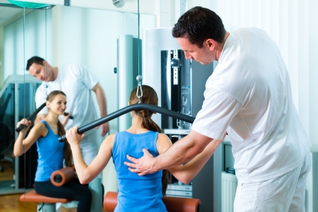 physical therapist: Patient at the physiotherapy making physical exercises with her therapist Stock Photo