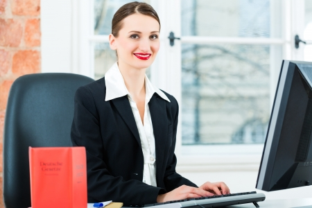 statutes: Young lawyer working in her Office, she is sitting behind folders writing into a file