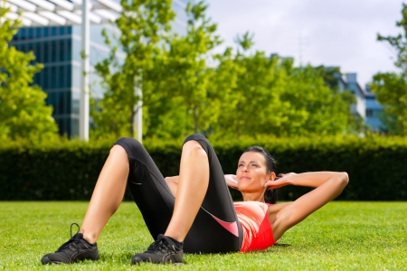 situp: Urban sports - young woman is doing warming up and sit-ups before running in the city  Stock Photo