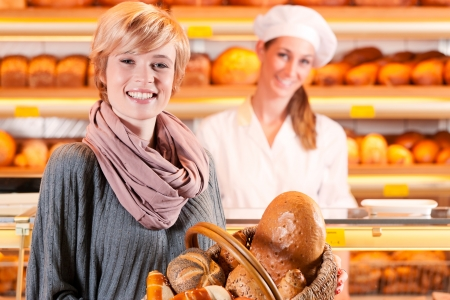 Female baker or saleswoman in her bakery with a female customer and fresh pastries or bakery products Stock Photo - 18498665