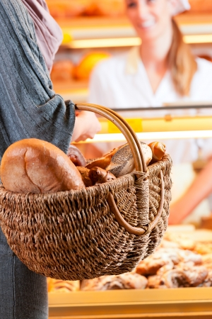 bakery shop: Female baker or saleswoman in her bakery with a female customer and fresh pastries or bakery products
