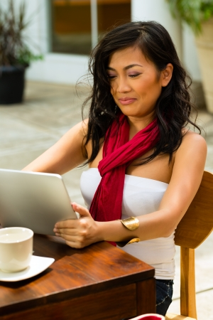 alone person: Asian woman is sitting in a bar or cafe outdoor and is surfing the internet with a tablet computer