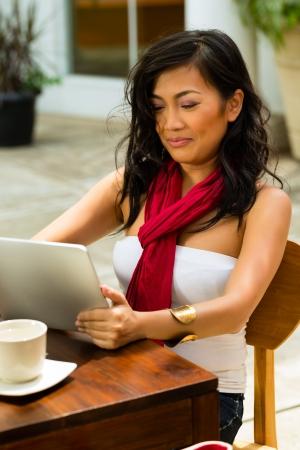 cafe internet: Mujer asiática está sentado en un bar o un café al aire libre y está navegando por Internet con un equipo Tablet PC