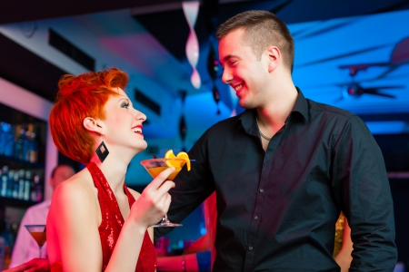 first date: young couple in bar or club drinking cocktails, it might be the first date Stock Photo
