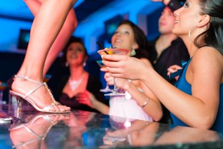 hôtesse: Les gens ayant une partie en club ou un bar, une femme danse sur la table Banque d'images