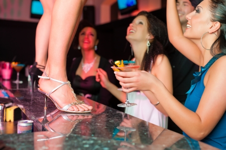 party outfit: People having a party in club or bar, one woman is dancing on the table