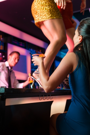 party outfit: People having a party in club or bar, two women are dancing on the table