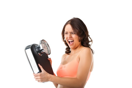 losing control: Diet and weight, young woman with a scale, she is desperate and shouting