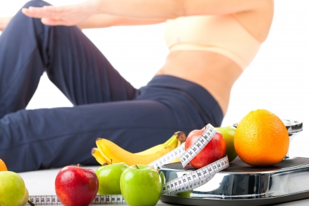 weight scale: Diet and sport - young woman is doing sit-ups next to a measuring scale, a measuring tape and fruits Stock Photo