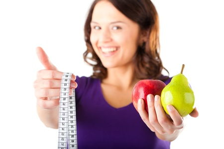 Healthy eating, woman with apple and pear and measuring tape photo