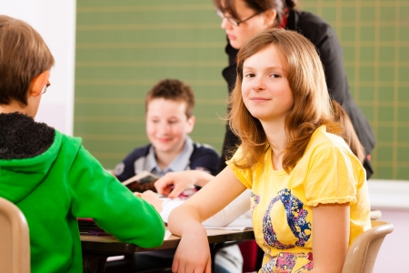 primary education: Education - Pupils and teacher learning at elementary or primary school in the classroom Stock Photo