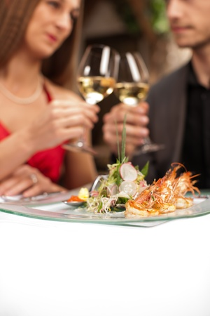 Focus on fresh prawns on plate with couple toasting in background. photo