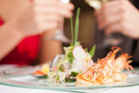 Close-up of fresh shrimps on plate with couple in background photo