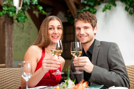 Portrait of happy couple having a drink during their meal photo