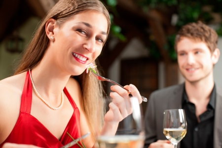 Portrait of attractive woman eating food with boyfriend sitting in background photo