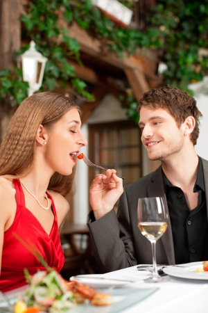 Couple on romantic date at a restaurant with food and wine photo