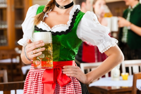 steins: Young people in traditional Bavarian Tracht in restaurant or pub, one woman is standing with beer stein in front, the group in the background Stock Photo