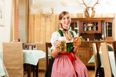 tracht: Young woman in traditional Bavarian Tracht in restaurant or pub with beer and steins and pretzel Stock Photo