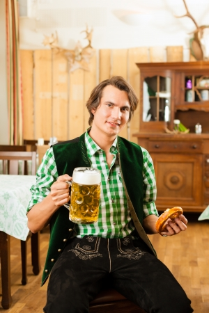 steins: Young man in traditional Bavarian Tracht in restaurant or pub with beer and steins and pretzel Stock Photo