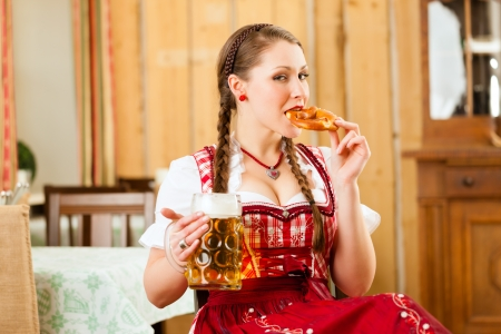 steins: Young woman in traditional Bavarian Tracht in restaurant or pub with beer and steins and pretzel Stock Photo