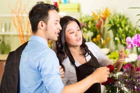 fullness: Friendly Asian florist or Saleswoman in a flower shop advising a customer Stock Photo