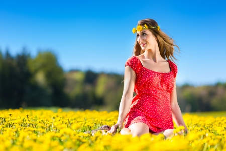 sunlit: Young girl sitting in spring on a flower meadow with dandelion