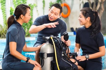 Asiaten an der Diver Kurs in Tauchschule in Neoprenanzug mit Sauerstoffflasche