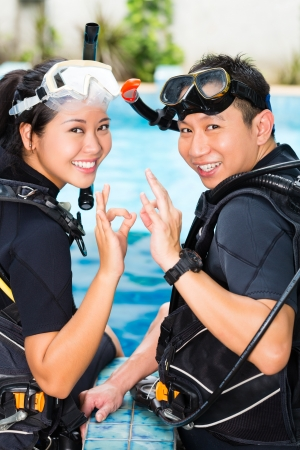 Asian people at the diver Course in diving school in wetsuit with an oxygen tank photo