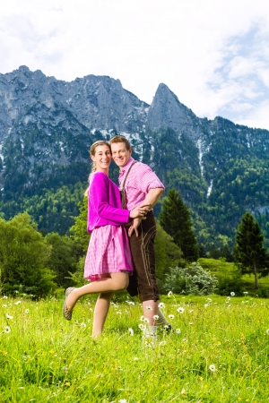 enyoing: Happy Couple in traditional dress is standing in the meadow with mountain panorama