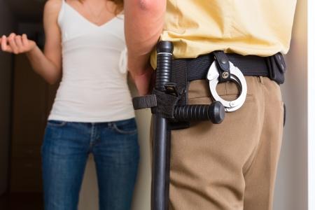 tocar la puerta: El oficial de polic�a en la puerta delantera de la casa de interrogar a una mujer o un testigo en relaci�n con una investigaci�n policial Foto de archivo