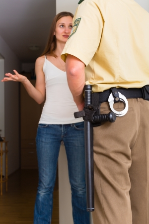 interrogation: Police officer at front door of home interrogating a woman or witness regarding a police investigation Stock Photo