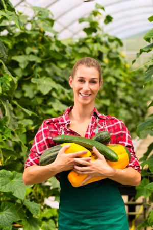 Female gardener at market gardening or nursery with apron and vegetables photo