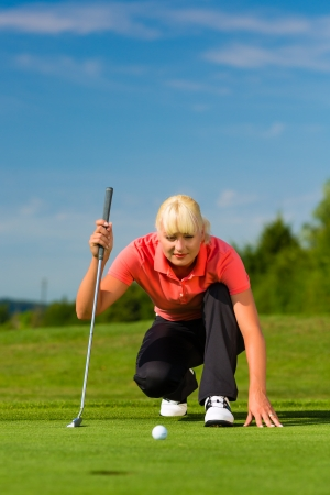 Young female golf player on course aiming for her put photo