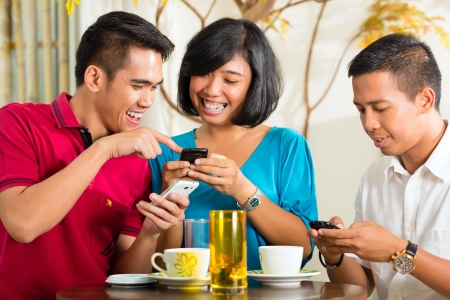 Asian people having fun together with mobile phone and drinking coffee or cocktail photo
