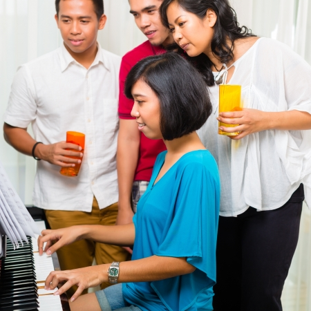 upright: Asian people sitting together at the piano and having fun and smiling